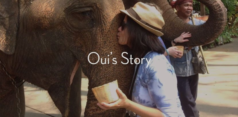 """Oui kissing an elephant with overlaying text """"Oui's Story"""""""